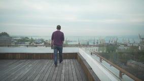 Темный с волосами человек в вскользь одеждах с журналом в руке идя на деревянную крышу смотря гавань seascape на пасмурный день акции видеоматериалы