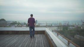 Темный с волосами человек в вскользь одеждах с журналом в руке смотря гавань seascape идя на деревянную крышу на пасмурный день акции видеоматериалы
