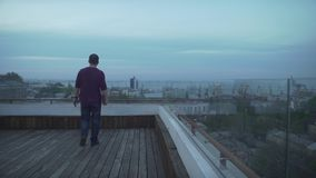 Темный с волосами человек в вскользь одеждах с журналом в руке смотря гавань seascape на пасмурный день идя на деревянную крышу видеоматериал