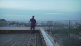 Темный с волосами человек в вскользь одеждах с журналом в руке смотря seascape гавани на пасмурный день идя на деревянную крышу сток-видео