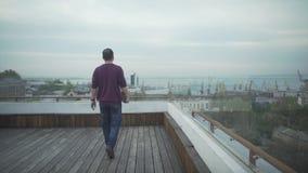 Темный с волосами человек в вскользь одеждах с журналом в руке смотря seascape гавани идя на деревянную крышу на пасмурный день видеоматериал