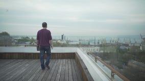 Темный с волосами человек с журналом в руке в вскользь одеждах идя на деревянную крышу смотря гавань seascape на пасмурный день сток-видео
