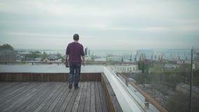 Темный с волосами человек с журналом в руке в вскользь одеждах идя на деревянную крышу смотря seascape гавани на пасмурный день акции видеоматериалы