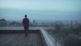 Темный с волосами человек с журналом в руке в вскользь одеждах смотря гавань seascape идя на деревянную крышу на пасмурный день видеоматериал