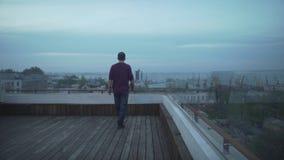 Темный с волосами человек с журналом в руке в вскользь одеждах смотря seascape гавани идя на деревянную крышу на пасмурный день видеоматериал