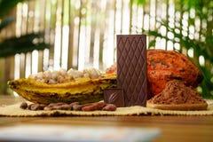 Темный шоколадный батончик, сырцовый плодоовощ какао, фасоли какао, масло какао на деревянном столе Стоковая Фотография