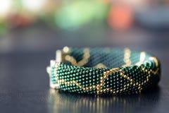 Темный ый-зелен вышитый бисером браслет с золотой картиной Стоковое Фото