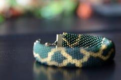Темный ый-зелен вышитый бисером браслет с золотой картиной Стоковые Изображения