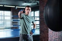 Темн-наблюданный боец тренируя крепко в спортзале Стоковое Изображение