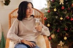 Темн-с волосами женщина представляя с стеклом шампанского в кресло-качалке Стоковая Фотография RF