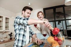 Темн-с волосами красивый человек в checkered рубашке имея потеху с овощами стоковое фото rf