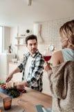 Темн-с волосами красивый человек в checkered рубашке имея потеху с овощами стоковая фотография rf