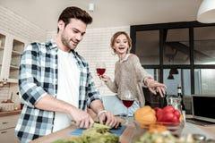 Темн-с волосами красивый человек в checkered рубашке режа овощи стоковые фотографии rf