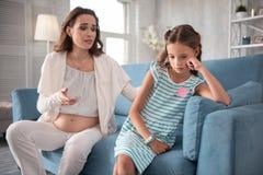 Темн-с волосами маленькая девочка не имея никакое настроение говоря к ее беременной матери Стоковая Фотография RF