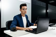 Темн-с волосами молодой архитектор одетый в работах синего пиджака на ноутбуке в офисе стоковые изображения