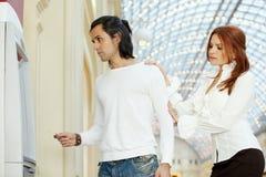 Темн-с волосами человек с кредитной карточкой и красн-с волосами женщина стоят Стоковые Фото
