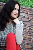Темн-с волосами девушка сидя на стенде Стоковое фото RF