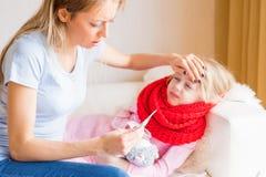 Температура мамы измеряя ее больной дочери стоковое фото