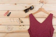 Тенденции моды - солнечные очки, красное платье в точках польки на вешалке и ювелирные изделия: ожерелье жемчуга, зажим жемчуга в стоковые изображения