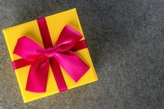 Тенденции подарка Думающ о подарки Новом Годе, дне рождества и валентинки и онлайн покупки Желтая коробка присутствующая с смычко Стоковые Фотографии RF
