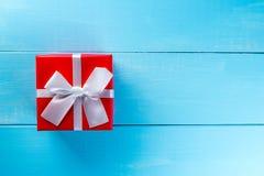 Тенденции подарка Думающ о подарки Новом Годе, дне рождества и валентинки и онлайн покупки Красная коробка присутствующая с смычк Стоковые Фотографии RF