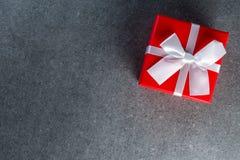Тенденции подарка Думающ о подарки Новом Годе, дне рождества и валентинки и онлайн покупки Красная коробка присутствующая с смычк Стоковая Фотография RF