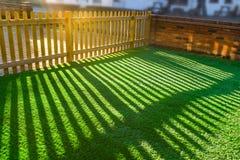 Тени деревянного частокола на искусственной лужайке травы Стоковая Фотография