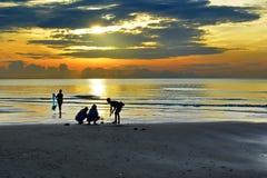 Тени людей удя на пляже на восходе солнца Стоковые Фото