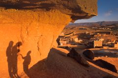 Тени на утесе и взгляд от холма к небольшой деревне на заходе солнца, провинции Ouarzazate, Марокко стоковые изображения