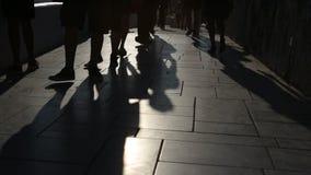 Тени людей идя в город Шествие улицы