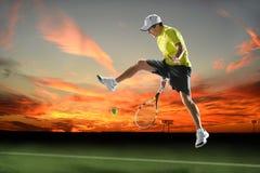 Теннисист в действии на заходе солнца Стоковые Фотографии RF