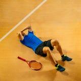 Теннисист заискивая вниз со смотреть нанесенный поражение и грустный стоковые изображения