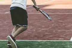 Теннисист молодого спорта мужской на практике летнего лагеря стоковое фото