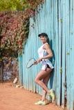 Теннисист, около голубой загородки Девушка держит ракетки тенниса Стоковое фото RF