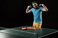 теннисист показывая мышцы пока стоящ на таблице тенниса с шахматной доской стоковые изображения
