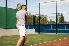 Теннисист beginner молодого человека делая спорт на суде на летний день стоковая фотография rf