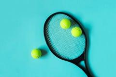Теннисные мячи и ракетка на голубой предпосылке Оборудование спорта стоковые изображения rf