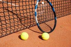 Теннисные мячи и ракетка на сети стоковое фото rf