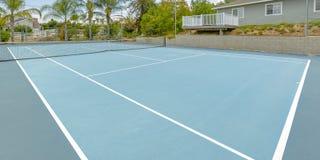 Теннисный корт с домами в окружающей територии стоковое фото