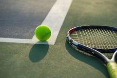 Теннисный мяч и ракетка под солнечным светом последнего вечера стоковые фото