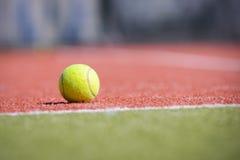 Теннисный мяч на апельсин-зеленом поле Стоковое Изображение RF