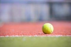 Теннисный мяч на апельсин-зеленом поле Стоковая Фотография RF