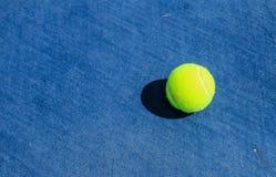 Теннисный мяч на голубом трудном суде стоковое фото