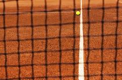 Теннисный мяч на теннисном корте Взгляд через сеть стоковые фотографии rf