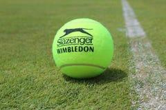 Теннисный мяч Slazenger Уимблдона на теннисном корте травы Стоковая Фотография RF