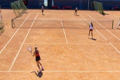 Теннис игры девушек на суде грязи Спаренная игра тенниса Молодые теннисисты Стоковая Фотография RF