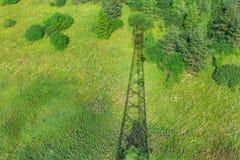 Тень башни радиосвязи с антеннами радио и спутниковыми антенна-тарелками на зеленом поле с травой, кустами и стоковое изображение
