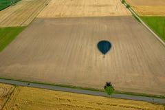 Тень воздушного шара летая над культивируемыми полями с целью дорог Стоковое Фото
