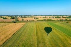 Тень воздушного шара летая над культивируемыми полями с целью безоблачного неба Стоковая Фотография