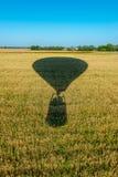 Тень воздушного шара летая над культивируемыми полями с целью безоблачного неба Стоковые Изображения